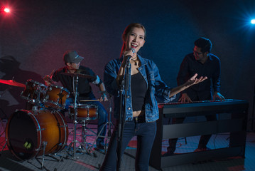 woman singer standing with music Band in dark and Lens flare effect