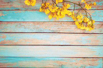 Wall Mural - Yellow flowers on vintage wooden background, border design. vintage color tone - concept flower of spring or summer background