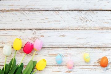 Wall Mural - Colorful Easter eggs with tulip flower on rustic wooden planks background. Holiday in spring season. vintage pastel color tone. top view composition.