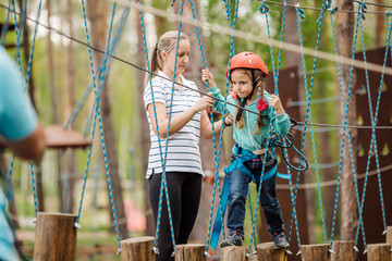 instructor helps the child on the rope road in the  training camp.