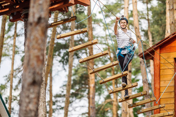 girl with climbing gear  in an adventure park are engaged in rock climbing or pass obstacles on the rope road.