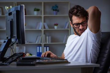 Young man staying late in office to do overtime work