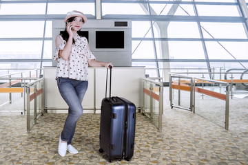 Young tourist with a mobile phone at airport