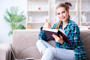 Female student reading the book  sitting on the sofa