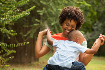 Young African American mother playing and her son.