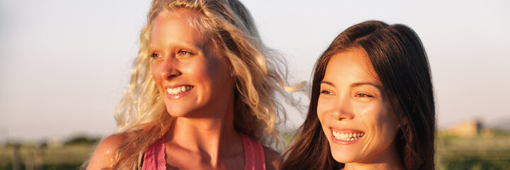 Perfect smiles multi ethnic women smiling. Asian chinese multiracial girl and caucasian blonde girlfriends portrait. Two beautiful young friends or couple. Banner panorama crop of faces.