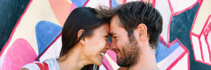 Young couple in love laughing together at Berlin wall, Germany, Europe travel. Portrait of happy multiracial people, Asian woman, Caucasian man kissing. Banner panorama on graffit background.