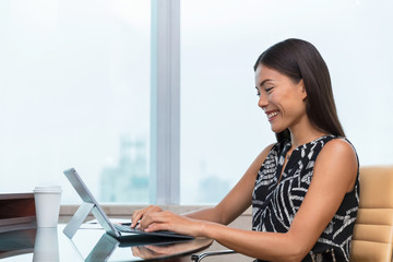 Asian business woman typing on laptop writing online working at office desk. Freelance remote work at home or customer service support. Businesswoman lifestyle.