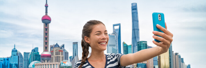 Wall Mural - China travel Asian girl tourist taking phone selfie photo on the Bund in Shanghai city vacation. Happy chinese young woman using smartphone app vlogging posting on social media. Multiracial person.