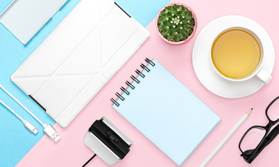 Flat lay photo of office desk with case for phone and tablet, notebook, tea mug, pencil, cactus, pink and blue background