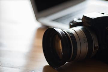 Eine Analoge Spiegelreflex Kamera und ein Laptop auf einem Tisch im Büro