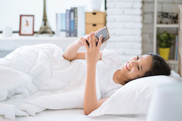 Asian girl she is relaxing, she is playing mobile phone in bed.