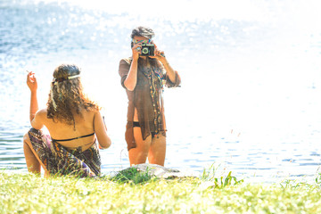 Hippie girls taking photos with an old camera and smoking - Vintage effect photo