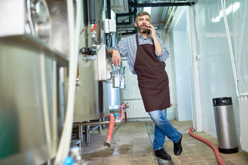 Full length portrait of handsome bearded brewer wearing apron standing at modern beer factory and talking to colleague on smartphone