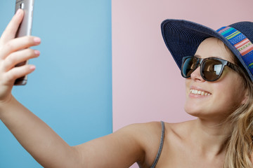 Pretty Young woman in hat and sunglasses with phone. Summer concept