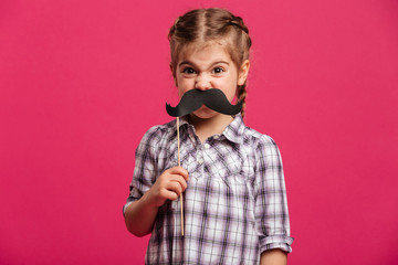 Angry funny little girl child holding fake moustache.