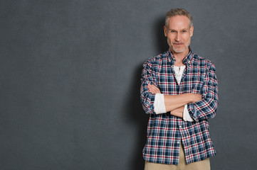 Mature man standing against grey wall