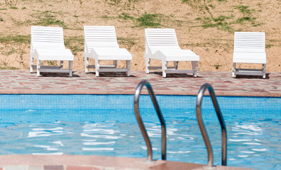 white sunbeds by the pool in the open air
