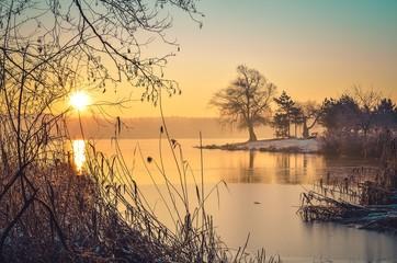 Beautiful winter landscape. Sunrise on the shore of the lake.