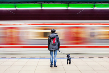 Lonely woman with dog at subway station platform with blurry moving train in background