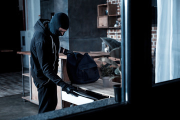 Professional burglar. Violent professional masked burglar wearing a black uniform and gloves and stealing a laptop from the table and holding a bag