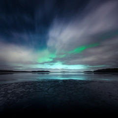 Northern Lights behind fast moving clouds in Kurjenrahka National Park, Finland