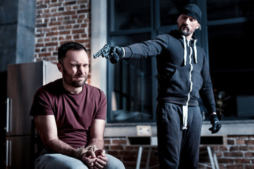 Killing. Scared panic bearded man sitting with his hands tied and eyes closed while a killer standing near him and holding a gun at his head