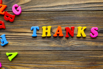 """colored text """"Thank you"""" on wooden background"""