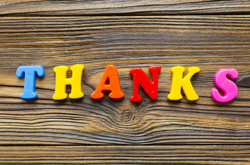 "colored text ""Thank you"" on wooden background"