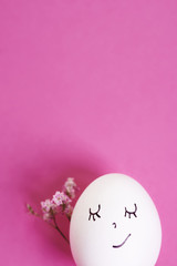 Egg with face isolated on pink bacground.