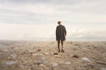lonely man walks towards an unknown destination in a desert landscape