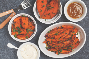 Different types of baked sweet potato with curry and a creamy garlic sauce. White utensils, dark background, top view. Healthy vegan food concept.