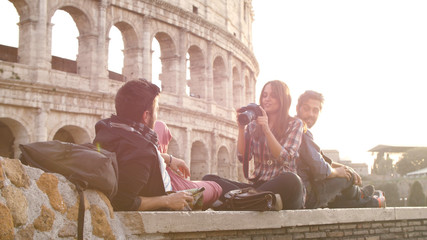 Three young friends tourists sitting lying in front of colosseum in rome at sunset taking pictures photos with dslr camera backpacks sunglasses happy beautiful girl long hair slow motion