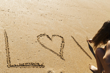 young woman writing the word love on the seashore in the sand of a beautiful beach