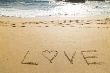 word love written on the seashore in the sand of a beautiful beach