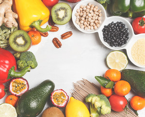 Healthy vegan food concept. Fruits vegetables background. Fresh vegetables, exotic and seasonal fruits, cereals, pasta, nuts and beans for a vegetarian diet, top view. Copy space, light background.