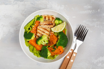 Salad with sweet potato, grilled tofu, broccoli and pecan. Healthy vegan food concept. Top view, light background, copy space.