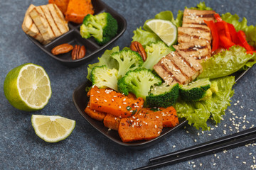 Vegetarian asian salad with sweet potato, grilled tofu, broccoli and pecan. Healthy vegan food concept. Dark background, copy space.