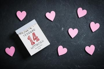 Abreißkalender mit Valentinstag und dekorativen Herzen auf Schieferuntergrund