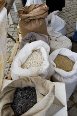 Sacks full with chickpeas, beans, buckwheat, millet, wheat, spelled, lentils, Einkorn wheat grains. Variety of beans, grains and seeds on a farmers market.