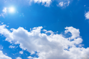 Blick auf wunderschöne scheinende Sonne an blauen Himmel mit weißen Wolken