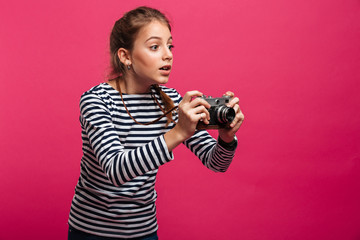 Shocked girl photographer holding camera. Looking aside.