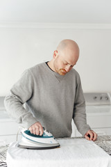 Front view of man ironing a towel