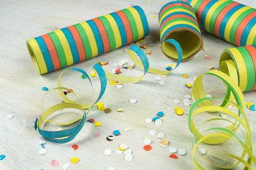 Carnival decoration, colorful streamers and confetti on wooden background