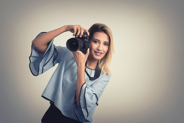 Cheerful young woman making photo on camera over gray background