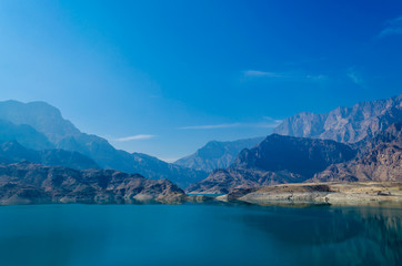 Waterscape with calm waters with reflection, mountains and blue sky on a bright sunny day, in Muscat, Oman.