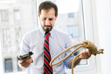Businessman choosing with which tool committing suicide