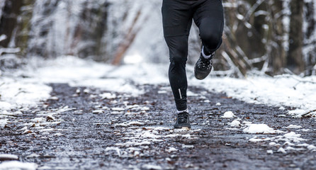 Legs of runner on snowy dirt, warm clothes for winter training