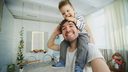 Happy father carrying his smiling son on neck and making selfie on smartphone in bedroom