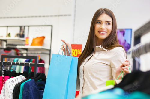 a3a7513f6f Portrait of beautiful young woman with shopping bags in clothing store.